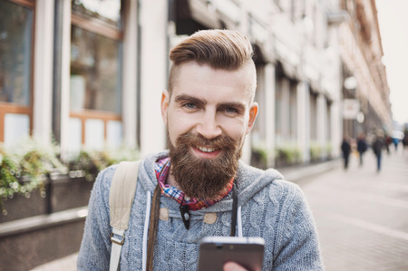 Portrait of modern young happy man using smart phone on the street