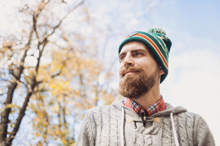 Cheerful young man wearing warm clothes standing outdoors Stock Photo