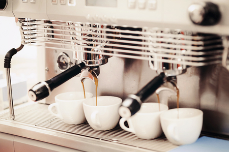 Close-up of espresso preparing in coffee machine. Professional coffee making, service and catering concept