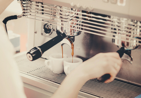 Barista preparing coffee in a coffee shop. Professional coffee making, service and catering concept Stock Photo
