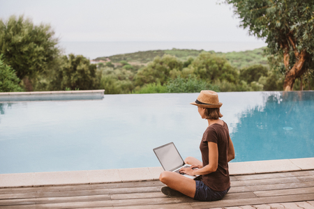 Young woman using laptop computer in hotel. Freelance work and travel concept. People using devices to plan trips, looking for hotels and flights, stay connected to family and office