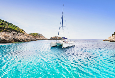 Beautiful bay with sailing boat catamaran, Corsica island, France 免版税图像 - 118934147