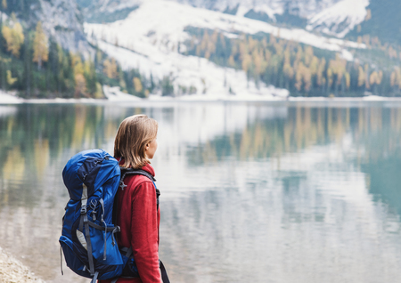 Young woman traveler in Alps mountains looking on a lake. Travel, winter and active lifestyle concept