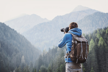 Young cheerful man photographer taking photographs with digital camera in a mountains. Travel and active lifestyle concept Stock Photo