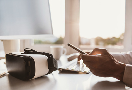 Business man using smartphone and computer with VR headset. Technology, IT, hi-tech, education concepts