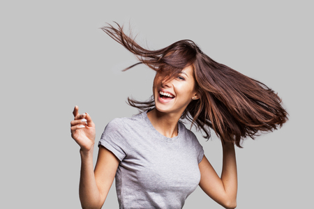 Beautiful girl with long hair laughing, dancing and enjoying life