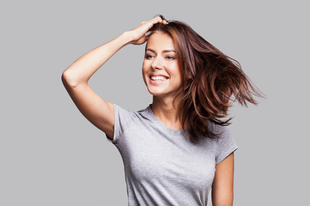 Attractive girl with long hair laughing, dancing and enjoying life