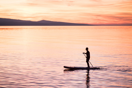 Silhouette of man at sunset standing on paddle board. Summer beach leisure activity. Active healthy lifestyle and travel summer concept