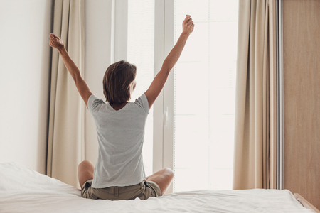 Woman stretching in bed after waking up, back view Stock Photo - 118934468