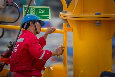 hombre pintando: Hombre que pinta una plataforma petrol�fera