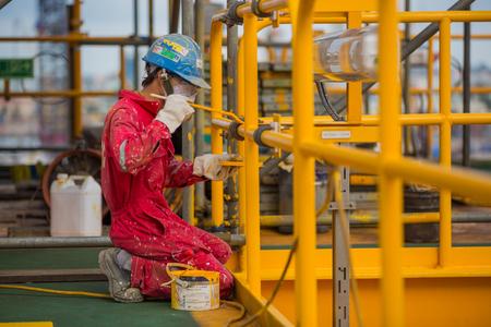 hombre pintando: Hombre que pinta una plataforma petrolífera