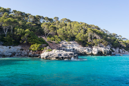 Bay with crystal blue water surrounded by cliffs and pine trees Stock Photo