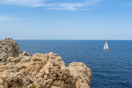 baleares: Boat sailing in front of a rocky cliff