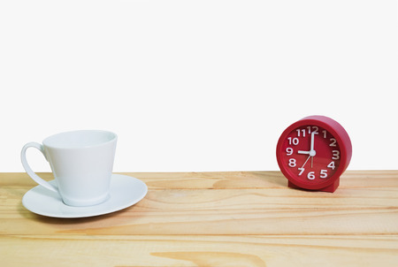 White cup of coffee  and red clock on wooden table with white background