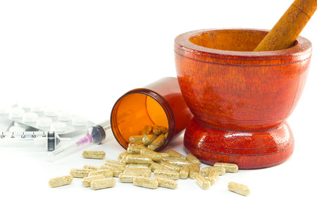 Mortar and pestle with herb capsules spilling out of bottle photo