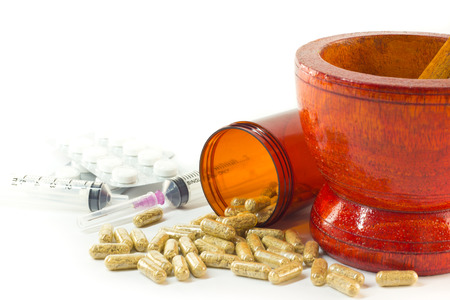 Mortar and pestle with herb capsules spilling out of bottle