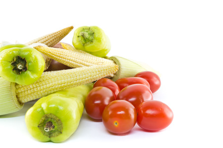 Stack of baby corn, green pepper, tomato and garlic