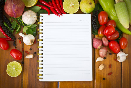 Fresh  vegetables and spices on a wooden background and paper photo