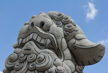 Looking up chinese stone lion statue on blue sky background photo