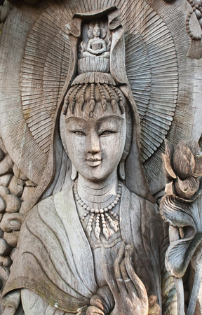 Kuan Yin image of buddha , Wood carving in Thailand photo