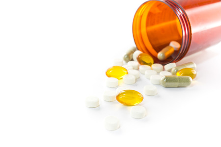 prescribe: Liquid capsules and pills spilling out of bottle on white background Stock Photo