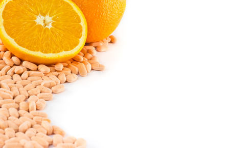 Orange fruit with vitamin c tablet on white background