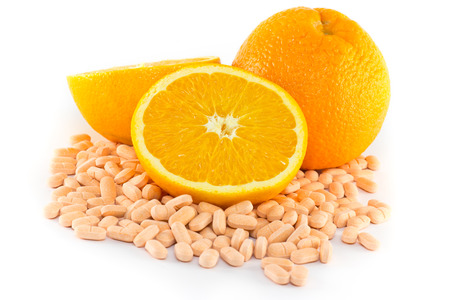 c to c: Orange fruit with vitamin c tablet on white background