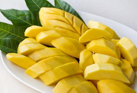 Ripe mango slice on white dish with green leaf photo