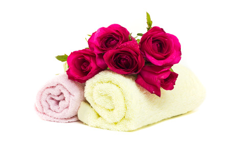 Roses on rolled up spa towels on white background photo