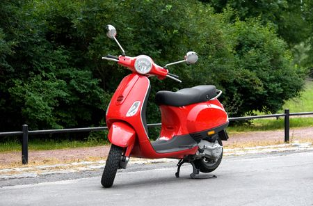 moped: One Red Scooter in the Park Stock Photo