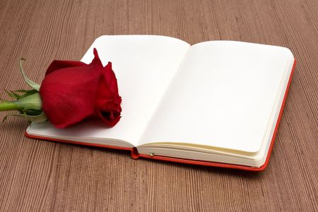 books on a wooden surface: Open Notebook with Red Rose