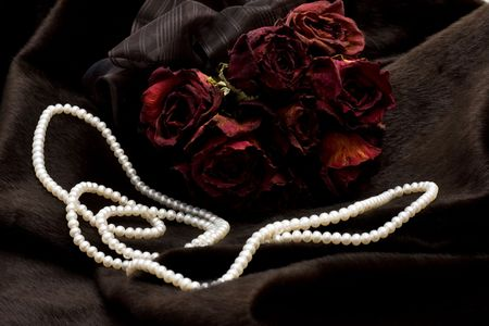 Bunch of dry red roses and pearls on black fur photo