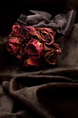 Bunch of red dry roses on black fur