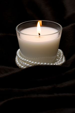 White candle in glass with pearls on black fur Stock Photo - 5606175