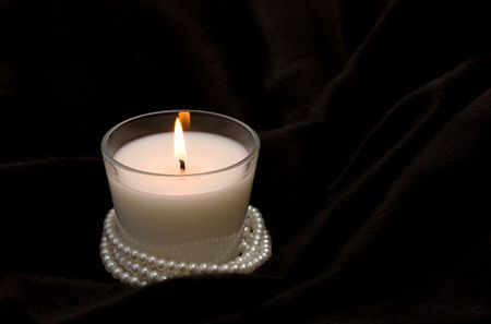 White candle in glass with pearls on black fur Stock Photo - 5606171