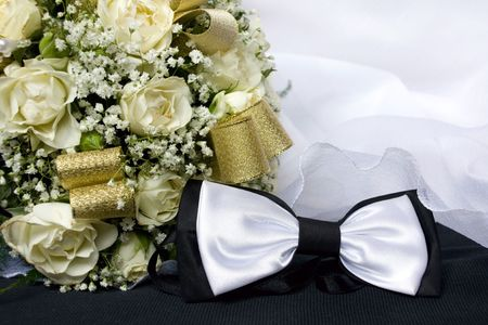 Bow tie and brides bouquet photo