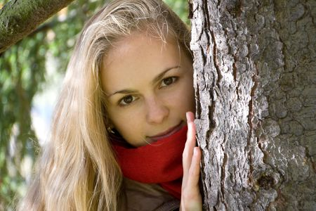 face in tree bark: Girl peeping out through pine tree