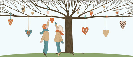 Boy and girl under Love tree with hanging hearts