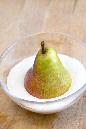 Pear and whipped cream in glass bowl photo