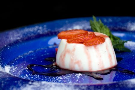 Delicious panna cotta dessert with strawberry, mint and chocolate sauce photo