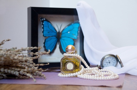 Perfume bottle and white pearl necklace photo