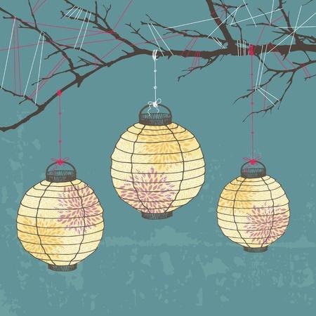 Three paper lanterns hanging on tree branch