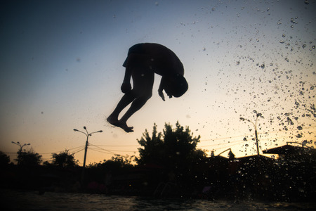man flying: Silhouette of a man flying over water Stock Photo