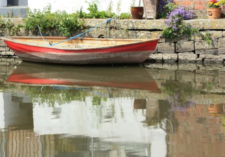 red and white boat tied up against a wall on a river