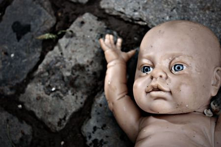 baby doll left on floor with oversharpening and vignette photo