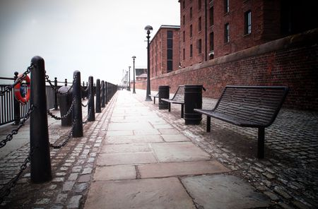 dark vignette of a bench on a footpath at liverpool docks Stock Photo
