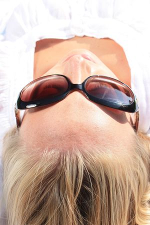 the head of a sun tanning woman with shades on
