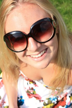 a pretty young woman tilting her head and smiling with glasses on Stock Photo