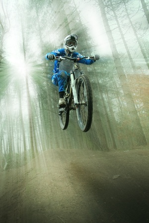 mountain biker jumping through the forest with light bursts coming through the trees behind him. Stock Photo