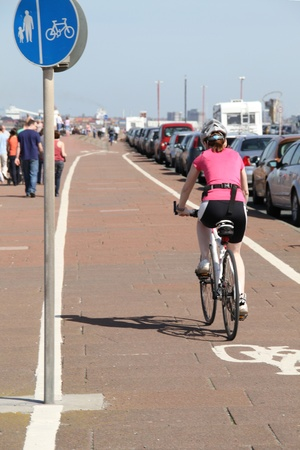 shot of a woman excercising on a bike outside in a dedicated cycle lane.